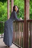 Mujer joven que se coloca cerca de la verja de madera en la naturaleza Fotografía de archivo