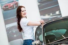 Mujer joven que se coloca cerca de un coche Imágenes de archivo libres de regalías