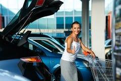 Mujer joven que se coloca con el carro de la compra y el pulgar para arriba cerca del Ca Imágenes de archivo libres de regalías