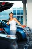 Mujer joven que se coloca con el carro de la compra y el pulgar para arriba cerca del Ca Fotografía de archivo