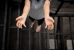 Mujer joven que se coloca con la mano que alcanza para arriba Foto de archivo