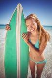 Mujer joven que se coloca con la tabla hawaiana en la playa Imágenes de archivo libres de regalías
