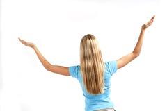 Mujer joven que se coloca con los brazos levantados Fotografía de archivo