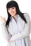 Mujer joven que se coloca con los pulgares para arriba que sonríen Fotografía de archivo