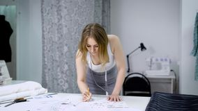 Mujer joven que se coloca de doblez sobre la tabla en estudio de la adaptación y que bosqueja los vestidos futuros El crear del d almacen de video