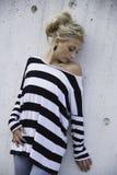 Mujer joven que se coloca delante de la pared blanca áspera Imagenes de archivo