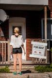 Mujer joven que se coloca delante de su nuevo apartamento Imagenes de archivo