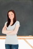 Mujer joven que se coloca delante de una pizarra Fotos de archivo