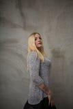 Mujer joven que se coloca delante del muro de cemento gris Fotos de archivo libres de regalías
