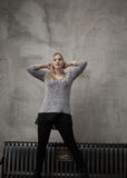 Mujer joven que se coloca delante del muro de cemento gris Fotografía de archivo