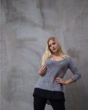 Mujer joven que se coloca delante del muro de cemento gris Foto de archivo libre de regalías