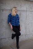 Mujer joven que se coloca delante del muro de cemento gris Imágenes de archivo libres de regalías