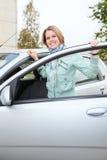 Mujer joven que se coloca detrás de un coche con la puerta abierta Foto de archivo