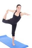Mujer joven que se coloca en actitud de la yoga en la estera de goma aislada en pizca Fotografía de archivo