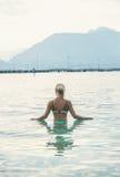 Mujer joven que se coloca en aguas de mar inmóviles de la mañana en Alanya Fotografía de archivo