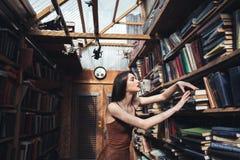 Mujer joven que se coloca en biblioteca Imagenes de archivo