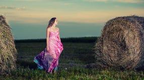 Mujer joven que se coloca en campo de la tarde encima Imágenes de archivo libres de regalías