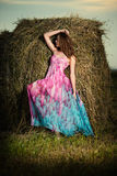 Mujer joven que se coloca en campo de la tarde encima Imagenes de archivo