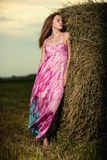 Mujer joven que se coloca en campo de la tarde encima Fotografía de archivo libre de regalías