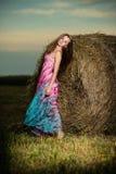 Mujer joven que se coloca en campo de la tarde encima Fotos de archivo