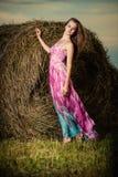 Mujer joven que se coloca en campo de la tarde encima Imagen de archivo libre de regalías