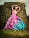 Mujer joven que se coloca en campo de la tarde sobre pajar pocilga de la moda Imagen de archivo