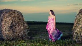 Mujer joven que se coloca en campo de la tarde sobre pajar pocilga de la moda Imagen de archivo libre de regalías