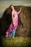 Mujer joven que se coloca en campo de la tarde sobre pajar pocilga de la moda Fotos de archivo