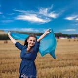 Mujer joven que se coloca en campo de trigo amarillo imagenes de archivo