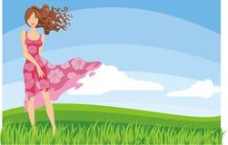 Mujer joven que se coloca en el campo verde Imagen de archivo