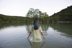 Mujer joven que se coloca en el lago Imagenes de archivo