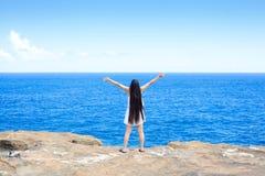 Mujer joven que se coloca en el océano de desatención del acantilado, brazos aumentados Fotografía de archivo libre de regalías