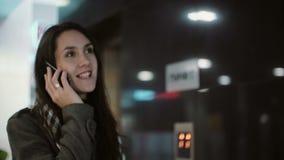 Mujer joven que se coloca en el pasillo de la oficina y que habla en el teléfono Hembra que usa smartphone y sonrisa almacen de video