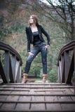 Mujer joven que se coloca en el puente Foto de archivo