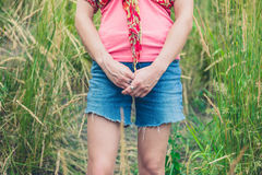 Mujer joven que se coloca en hierba alta Foto de archivo libre de regalías