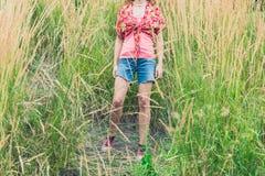 Mujer joven que se coloca en hierba alta Imagenes de archivo