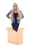 Mujer joven que se coloca en la caja de cartón aislada en blanco Foto de archivo libre de regalías