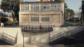 Mujer joven que se coloca en la mansión del balcón con la opinión aérea del parque de la ciudad del verde de la visión metrajes