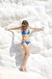 Mujer joven que se coloca en la pared blanca de la nieve Imágenes de archivo libres de regalías