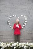 Mujer joven que se coloca en la pared con las bolas en forma de corazón de la nieve Fotos de archivo