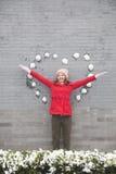 Mujer joven que se coloca en la pared con las bolas en forma de corazón de la nieve Fotos de archivo libres de regalías