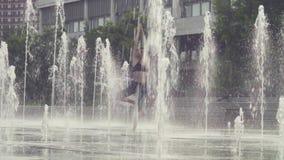 Mujer joven que se coloca en la posición del árbol dentro de la fuente