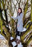 Mujer joven que se coloca en la rama del árbol Imágenes de archivo libres de regalías