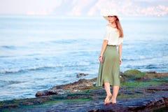 Mujer joven que se coloca en la roca fotografía de archivo libre de regalías