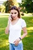 Mujer joven que se coloca en parque y que habla en su teléfono Imagenes de archivo