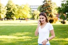 Mujer joven que se coloca en parque y que habla en su teléfono Foto de archivo