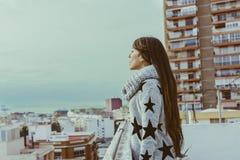 Mujer joven que se coloca en perfil en el tejado, mirando la ciudad, imágenes de archivo libres de regalías
