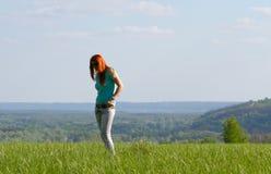 Mujer joven que se coloca en prado de la primavera Imágenes de archivo libres de regalías
