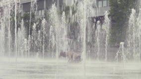 Mujer joven que se coloca en su cabeza dentro de la fuente