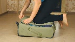 Mujer joven que se coloca en sus rodillas en la maleta sobrellenada, intentando cerrarla metrajes